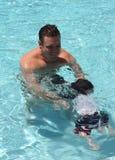 De vader onderwijst zoon om te zwemmen Stock Foto