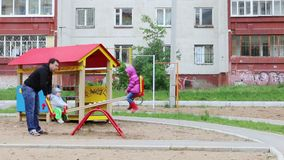 De vader slingert weinig dochter en zoon op geschommel bij speelplaats in bewolkte dag stock footage