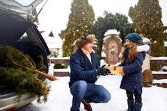 De vader stelt dochter voor een giftdoos in openlucht op sneeuw de winterdag Kerstboom in grote boomstam van familieauto Meisje royalty-vrije stock foto's