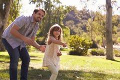 De vader Teaching Daughter To werpt Frisbee in Park royalty-vrije stock afbeeldingen