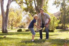 De vader Teaching Son To werpt Frisbee in Park stock fotografie