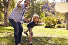 De vader Teaching Son To werpt Frisbee in Park royalty-vrije stock foto's