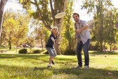 De vader Teaching Son To werpt Frisbee in Park stock foto's