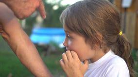De vader toont zijn dochter een beet van een insect op wapen De dochter is angst aangejaagd stock footage