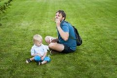 De vader toont zijn zoon hoe te om zeepbels te blazen Royalty-vrije Stock Foto