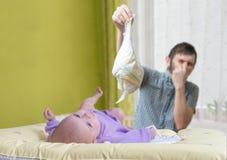 De vader verandert stinky luiers Zorg van baby met diarree Stock Fotografie