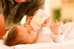 De vader voedt de baby Stock Afbeeldingen