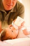 De vader voedt de baby Royalty-vrije Stock Afbeeldingen