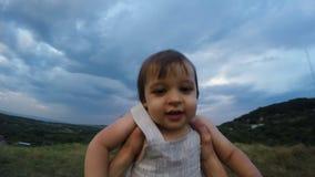 De vader werpt en draait omhoog zijn zoon op de berg in de avond stock footage