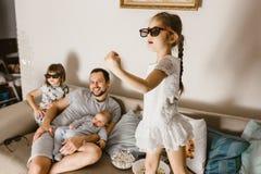 De vader zit op de bank met baby op zijn wapens en zijn twee dochters die in de speciale glazen op TV naast hem letten stock afbeelding