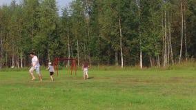 De vader, de zoon en de dochter spelen met bal op groen gebied met voetbalpoort bij de zomer stock videobeelden