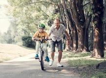 De vaderhulp zijn zoon leert om fiets te berijden stock afbeelding