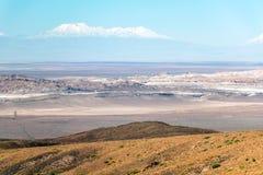 De vage achtergrond van Atacama-Woestijnlandschap met snow-capped Andesvulkanen, zout vlak en wat vegetatie op horizon, Chili royalty-vrije stock foto