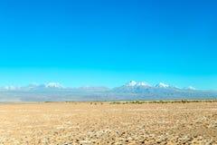 De vage achtergrond van Atacama-Woestijnlandschap met snow-capped Andesvulkanen, zout vlak en wat vegetatie op horizon, Chili stock foto