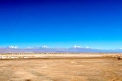 De vage achtergrond van Atacama-Woestijnlandschap met snow-capped Andesvulkanen, zout vlak en wat vegetatie op horizon, Chili stock fotografie