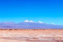 De vage achtergrond van Atacama-Woestijnlandschap met snow-capped Andesvulkanen, zout vlak en wat vegetatie op horizon, Chili royalty-vrije stock foto's