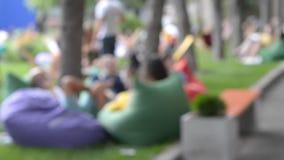 De vage Achtergrondmensenrust ontspant als zakvoorzitter, leunstoelenzakken in het park stock videobeelden