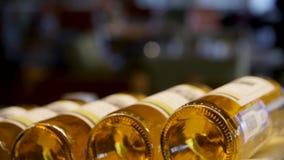 De vage flessen wit en namen wijn keurig worden opgemaakt op een rij op een plank in een grote supermarkt toe Heldere Samenvattin stock footage