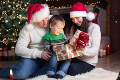 De vakantie, stelt, Kerstmisconcept - gelukkige moeder, vader en jong geitjejongen het openen giftdoos voor royalty-vrije stock afbeelding