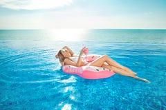 De vakantie van de zomer Vrouw in bikini op de opblaasbare doughnutmatras in het KUUROORD zwembad Royalty-vrije Stock Foto's
