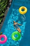 De vakantie van de zomer Vrouw die van Vakantie genieten, die in Zwembad drijven Stock Foto's