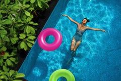 De vakantie van de zomer Vrouw die van Vakantie genieten, die in Zwembad drijven Stock Fotografie