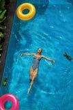 De vakantie van de zomer Vrouw die van Vakantie genieten, die in Zwembad drijven Stock Afbeeldingen