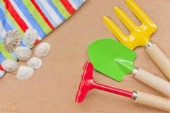 De vakantie van de zomer, zand, zeeschelpen, handdoek, speelgoed. Royalty-vrije Stock Afbeeldingen