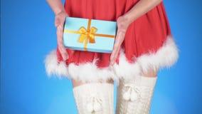 De vakantie van Kerstmis jonge aantrekkelijke vrouw in een kostuum van het sneeuwmeisje met een gift, die op een blauwe achtergro stock videobeelden