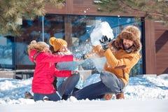 De vakantie van de winter Familietijd die samen in openlucht werpend sneeuw het vechten het lachen verrast close-up zitten stock afbeeldingen