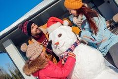 De vakantie van de winter Familietijd die zich samen in openlucht dichtbij huis bevinden die de sjaal van het sneeuwmanmeisje bli royalty-vrije stock afbeeldingen