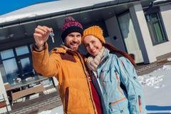 De vakantie van de winter Jong paar die zich in openlucht met sleutels van het nieuwe flat gelukkig glimlachen verenigen stock foto's