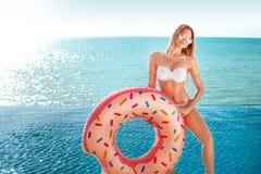 De vakantie van de zomer Het genieten van bruine kleur van vrouw in witte bikini met doughnutmatras dichtbij de oceaan royalty-vrije stock foto