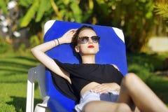 De vakantie van de zomer Het maniermeisje in zonglazen ontspant Op de achtergrond een palm Het concept van de vakantie Het mooie  royalty-vrije stock fotografie
