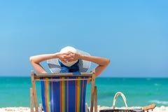De vakantie van de zomer Mooie jonge Aziatische vrouw die en gelukkig op ligstoel met het sap van de cocktailkokosnoot in de blau stock afbeeldingen