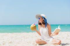 De vakantie van de zomer De ruikende Aziatische vrouwen die, het lezen boeken en het drinken kokosnotencocktail op het strand ont royalty-vrije stock foto's