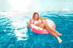 De vakantie van de zomer Vrouw in bikini op de opblaasbare doughnutmatras in het KUUROORD zwembad stock fotografie