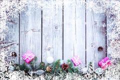 De de vakantieachtergrond van de Kerstmiswinter met giftenvakjes met spar vertakt zich, denneappels, Nieuwjaarballen op houten li royalty-vrije stock afbeelding