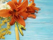 De vakantieflora van het lelie mooie oranje seizoen een blauwe houten wijnoogst als achtergrond stock foto's