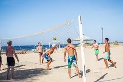 De vakantiegangermensen spelen in strandvolleyball Stock Foto's