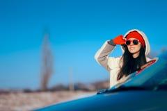 De Vakantiemeisje die van de de wintertoerist zich naast Haar Auto bevinden royalty-vrije stock fotografie