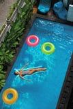 De vakanties van de zomer Vrouw Zonnebaden, die in Zwembadwater drijven Royalty-vrije Stock Afbeeldingen