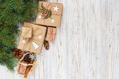 De vakjes van de Kerstmisgift en sparrentak met mand op houten lijst Stock Foto's