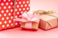De vakjes van de vakantiegift in het bewerken van document en rode stippen op roze achtergrond worden ingepakt die Concept mooie  royalty-vrije stock afbeeldingen
