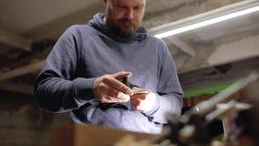 De vakman behandelt een houten kam op een vliegtuig, verwijderend overmaat rond de randen handmade 4 K stock videobeelden