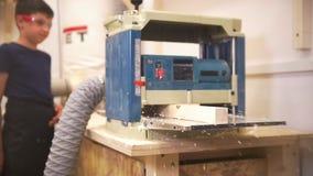 De vakman gaat een houten straal door de de timmerwerk malende machine, tienerjongen status dichtbij en het letten op over stock footage