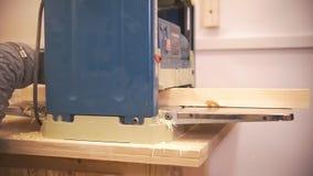 De vakman gaat een houten straal door de timmerwerkmachine over stock footage