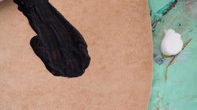 De vakman giet een verf en kleurt het gesneden leer voor handtas stock footage