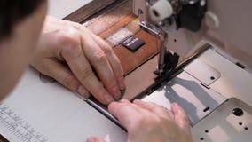 De vakman naait de textielzak voor handtas op naaimachine stock videobeelden