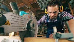 De vakman is scherp hout met een cirkelzaag stock footage